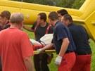 Hasiči a záchranáři nakládají do vrtulníku mladou ženu, která se popálila, když...