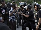 Policice hlídá dav lidí, který se sešel, aby vyjádřil nesouhlas s osvobozením