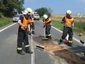 Hasiči po nehodě uklízejí silnici. (17.7.2013)
