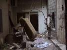 Voj�k Syrsk� svobodn� arm�dy mluv� s kolegou skrze d�ru ve zdi ve m�st� Deir...