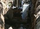 Bagr se snaží dostat k prasklému vodovodnímu řadu v Kobylisích