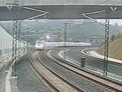 Záběr z bezpečnostní kamery - vlak rychle vjíždí do oblouku trati u města...