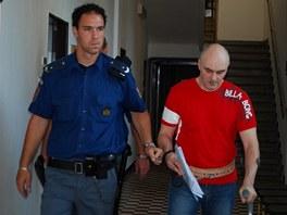 Justiční stráž přivádí Petra Rohela, obžalovaného z vraždy, do jednací síně.