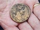 Archeolog ukazuje římskou minci Sestertius z roku 30 n. l. s portrétem císaře