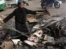 Egypťanka prohledává spáleniště na káhirském náměstí Nahda. Na zemi jsou...