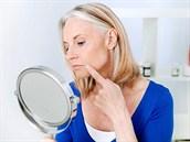 Žena zkoumá vrásky v zrcadle