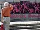 Muž si prohlíží narůžovo nabarvený památník Rudé armády v bulharské Sofii. (21.