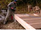 Petr Kubala při práci na dřevěném roštu podlahy domu