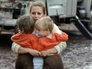 Žena odnáší své děti do bezpečí s pomocí hasiče z Juniper Valley Fire Crew v