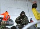 Příslušník pobřežní stráže míří pistolí na aktivisty Greenpeace. (18. září 2013)