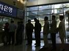 Jihokorejci čekají ve frontě před směrnánou, aby si před návratem do práce v...