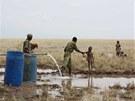 Keňský policista podává vodu žíznivému dítěti u vrtu v Lotikipi. (Keňa, září