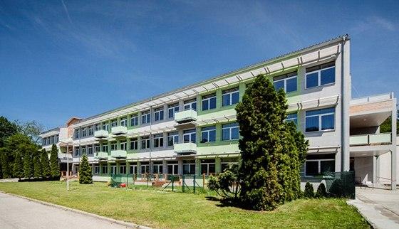 Ze školy se stal příjemný pasivní bytový dům stojící v zeleni.