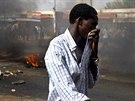 Na snímku si muž zakrývá obličej před kouřem z hořících pneumatik, které na...