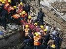 Záchranáři vyprošťují raněné z trosek budovy, jež se zřítila v pátek ráno v...