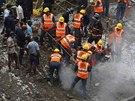 Záchranáři již z trosek zřícené budovy vynesli tělo jedné oběti (27. září 2013).