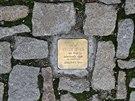 Drobné měděné destičky, splývající v chodníku s ostatními kameny. To jsou dva...