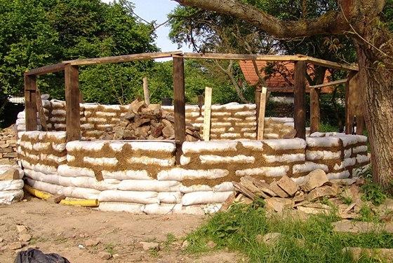Nosná konstrukce letní kuchyně z darovaných trámů a zdi z napytlované hlíny