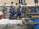 Italští vojáci vynáší z lodi těla afrických běženců, kteří utonuli u Lampedsuy...