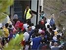 Uprchlíci, kterým se z potápějící se lodi podařilo vyváznout, zůstávají na