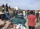 V lampeduském přístavu vedle sebe leží vyskládaná těla afrických uprchlíků,...