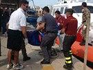Záchranáři na Lampeduse vynáší ze člunu do pytle zabalené tělo oběti. (3. října...