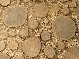 Podlahu tvoří špalky z palivového dříví zasazené ve štěrku, co zbyl po