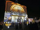 Diváci sledují projekci na budově znovuotevřeného kina Eden (9. října 2013)