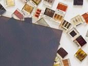 330 nanometr� siln� film perovskitu na skle. To je z�kladn� aktivn� prvek nov�ch �l�nk� s ��innost� 15 procent. V pozad� jsou r�zn� typy pokusn�ch �l�nk� z jin�ch materi�l�.