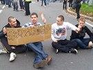 Někteří z demonstrantů se na protest proti zablokování průvodu posadili na...