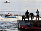 Neohrožení záchranáři na člunu zachraňují dvojici žen uvězněných u jezu na...