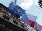 Voliče vítá kromě české vlajky i vlajka EU a červená vlajka označující českou...