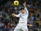 BALE VE VZDUCHU. Gareth Bale (v bílém) bojuje ve vzduchu o míč s Adrianem Correiou z Barcelony.