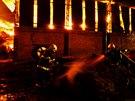 Hasiči prolévají vodou slámu z hořící haly v Brodku u Prostějova, která celá...