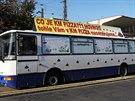 Kloubový autobus s vulgárními nápisy a figurou oběšence (leží za bannerem),...