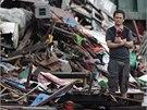 Následky řádění tajfunu na Filipínách. Jeden z obyvatel zasaženého města stojí