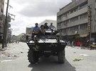 Ve městě Tacloban poničeném tajfunem Haiyan hlídkuje ozbrojená patrola. Lidé...