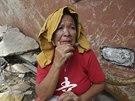 Filipínka, která přežila řádění tajfunu, sleduje zkázku u lodi vyvržené na souš...