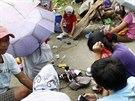 Lidé v Taclobanu si nabíjejí telefony díky natažené prodlužovačce.