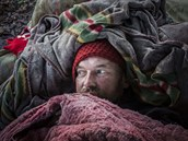 Nemocný Polák, který p�i�el o domov, se choulil ve starých dekách a pe�inách.