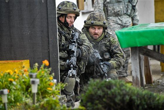 České jednotky pročesávají dobytou vesnici během cvičení Sabre Junction II v