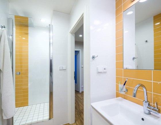 Bílou koupelnu oživuje žlutý obklad 10 × 30 cm.