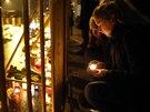 Lidé přicházejí k troskám zříceného nákupního centra v Rize, aby tam zapálili