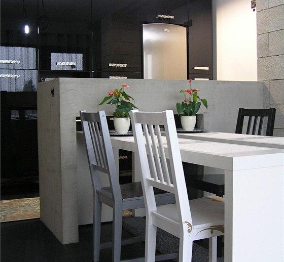 Jídelní stůl lze zasunout částečně pod ostrůvek. Po vysunutí u něj může sedět