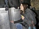 Milujeme Ukrajinu! Mladá demonstrantka píše svůj vzkaz na štít těžkooděnců (3....
