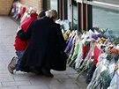 Lidé nosí k budově naproti baru, kde zemřelo při havárii vrtulníku nejméně 9