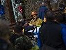 Záchranáři odvážejí muže na lehátku od vlaku, který vykolejil v Bronxu (New...