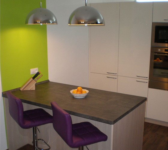Barevně neutrální kuchyni oživuje výrazný barevný pruh u ostrůvku a vínové