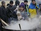 Jedna z demonstrantek v centru Kyjeva připravuje jídlo, které je zájemcům k...