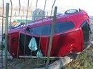 Peugeot 206 prorazil plot a skončil na levém boku. (17. prosince 2013)